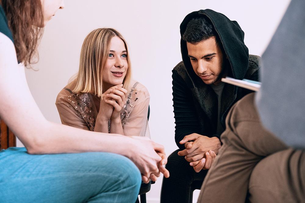 Jongeren zitten in een kring en overleggen